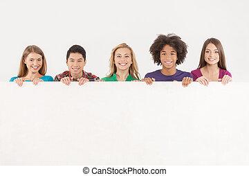 friends, mit, kopie, space., heiter, junger, multi-ethnisch, leute, besitz, kopieren platz, und, lächeln, kamera, während, freigestellt, weiß