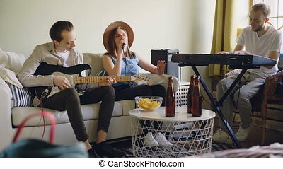 Friends musicians are practising at home singing and playing guitar and keyboard. Musical instruments, attractive creative people, friendship and hobby concept.