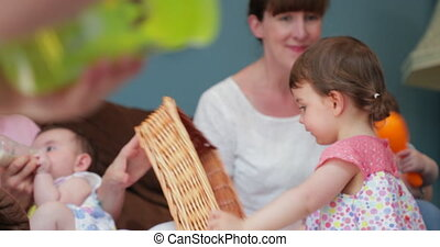 Friends mutil task between talking and feeding their child -...