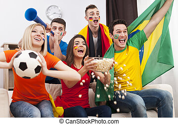 Friends of different nations celebrating goal of favourite team