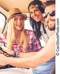 Friends on road trip. Three cheerful young people looking at camera and smiling while sitting inside of their minivan