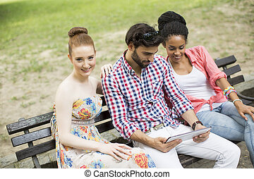Friends on the bench with tablet