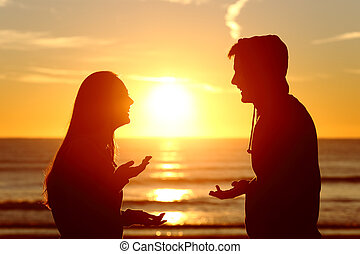Friends or couple of teens talking happy at sunset