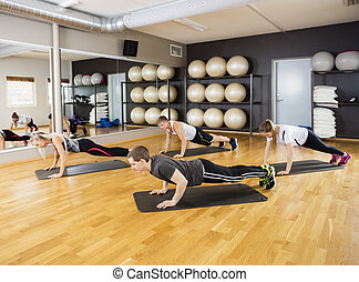 Friends Performing Plank Exercise In Gym