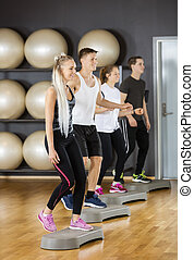 Friends Performing Step Aerobics Exercise In Gym