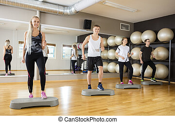 Friends Performing Step Exercise In Gym