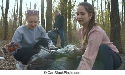 Young volunteers collecting garbage in park