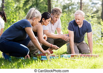 Friends Planning While Playing With Building Blocks On Grassy Fi