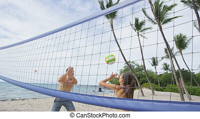 Friends Playing Beach Volleyball On Beach. Young people having fun playing recreational game in summer.