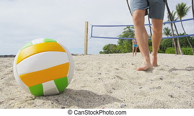 Friends playing beach volleyball sport having active fun living healthy lifestyle. Man player picking up ball walking during volley ball after game in summer. Woman and man fitness model doing sport.