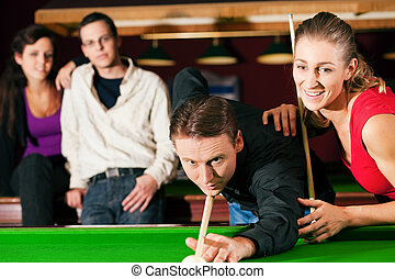 Friends playing billiards together - Group of four friends...
