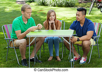 Friends playing cards in a garden