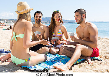 Friends playing cards on the beach