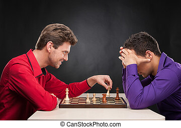 friends playing chess on black background. smiling young man...