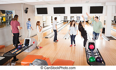 Friends Playing in Bowling Alley - Group of happy friends...
