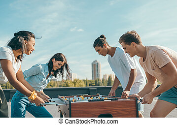 friends playing table football - group of happy friends...