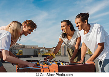 friends playing table football - happy young friends playing...