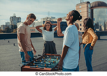 friends playing table football - young friends playing table...