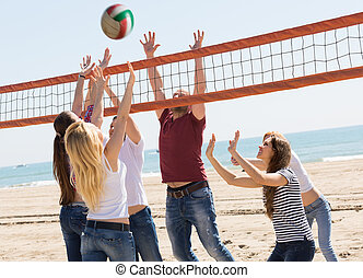 Friends playing beach volleyball. Group of three friends ...