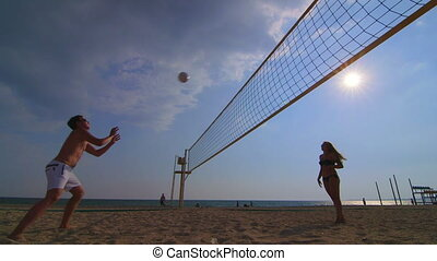 Friends playing volleyball on summer beach