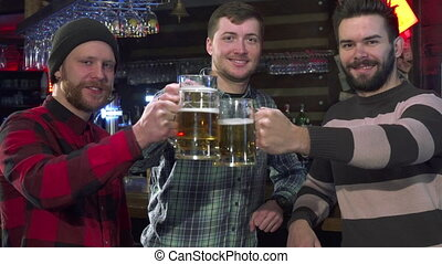 Friends pose with glasses of beer at the pub