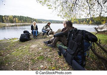 Friends Preparing For Lakeside Camping
