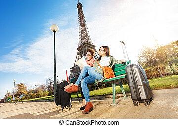 Friends reading map sitting near the Eiffel Tower