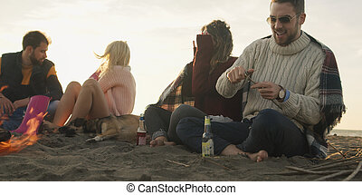 Friends Relaxing At Bonfire Beach Party