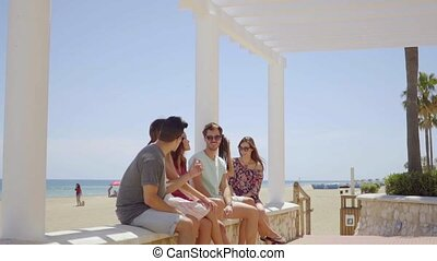 Friends relaxing on a covered seafront promenade - Young...