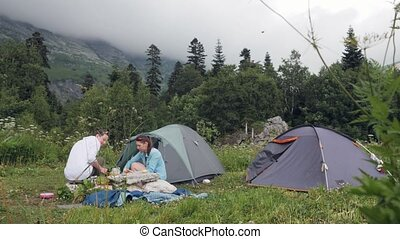 Friends resting in summer camping while tourist hike in...