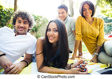 Friends resting outdoors in campus - Portrait of a happy ...