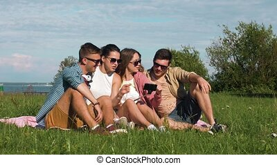 friends reviewing pictures on smartphone at park -...