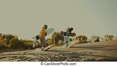 Friends run with sandboards in desert - Tourists Sand Skiing...