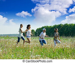 Friends running in meadow - Four friends running at meadow ...