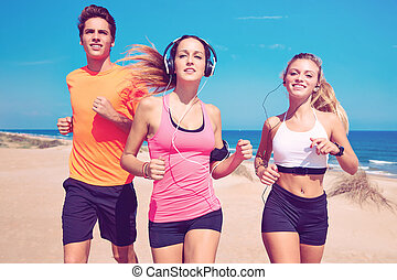 friends running on the beach happy in summer