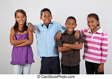 Group of four happy young ethnic school children ages 9 and 10 share a moment together in studio posing for pictures