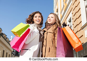 Friends shopping. Low angle view of happy two young women standing with their hands raised and holding the shopping bags