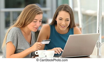 Friends shopping online paying with card