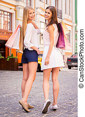 Friends shopping. Rear view of two beautiful young women holding shopping bags and looking over shoulder with smile while standing outdoors