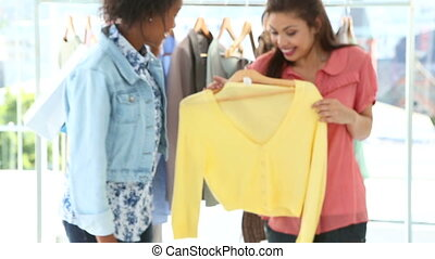Friends shopping together and laughing at camera in a clothing store