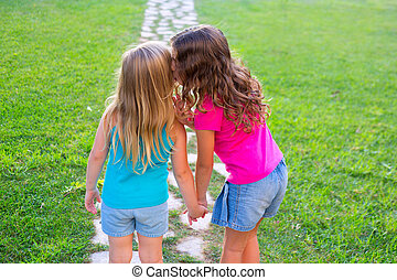 friends sister girls whispering secret in ear in garden