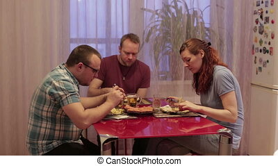 Friends sit at the table and dinner