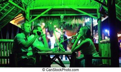 Friends sitting in beach Hookah Bar, Man smokes talk and laugh. 1920x1080