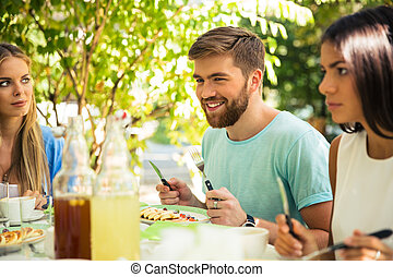 Friends sitting in outdoor restaurant