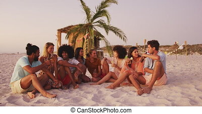 Front view of a multi-ethnic group of friends on holiday enjoying time together on a tropical beach at sundown, talking and smiling, in slow motion