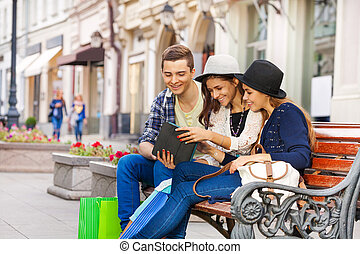 Friends sitting together with tablet on the bench