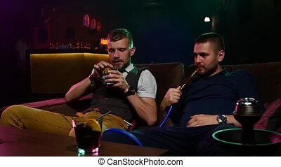 friends smoke from shisha pipei n the lounge caffee. Slow motion