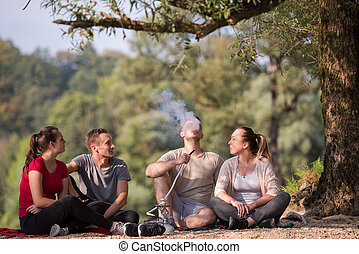 friends smoking hookah on the river bank