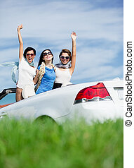 Friends stand in the cabriolet with hands up