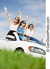Friends stand in the white car with hands up